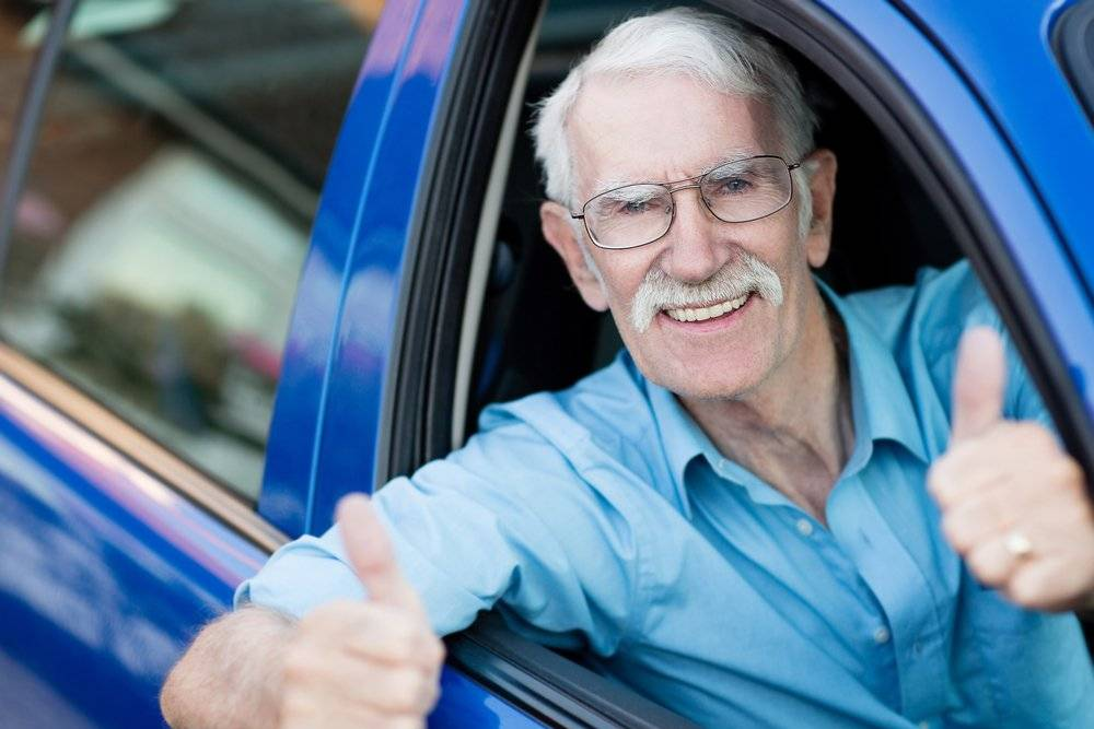 Man driving a car and showing thumbs up